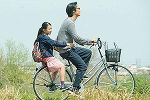 Film Still CLOSE-KNIT – Karera ga Honki de Amu toki wa von Naoko Ogigami mit Tôma Ikuta, Eiko Koike, Kenta Kiritani und Rin Kakihara; die 11-jährige Tomo (gespielt von Rin Kakihara) fährt auf dem Fahrradgepäckträger ihres Onkels Makio (gespielt von Kenta Kiritani) durch die japanische Kirschblüte