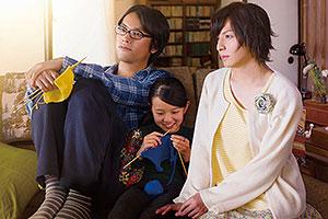 Film Still CLOSE-KNIT – Karera ga Honki de Amu toki wa von Naoko Ogigami mit Tôma Ikuta, Eiko Koike, Kenta Kiritani und Rin Kakihara; die 11-jährige Tomo (gespielt von Rin Kakihara) sitzt strickend zwischen ihrem Onkel Makio (gespielt von Kenta Kiritani) und dessen Freundin Rinko (Tôma Ikuta)