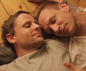 Film Still EIN WEG - PATHS von Chris Miera; Andreas Haller (gespielt von Mike Hoffmann) und Martin Winter (gespielt von Mathis Reinhardt) liegen mit geschlossenen Augen aneinander gekuschelt auf einem Holzboden