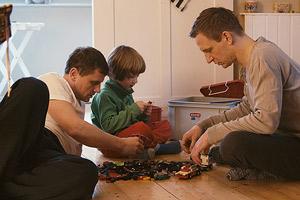 Film Still EIN WEG - PATHS von Chris Miera; Andreas Haller (gespielt von Mike Hoffmann) und Martin Winter (gespielt von Mathis Reinhardt) spielen mit ihrem Sohn auf dem Fußboden
