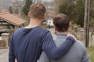 Film Still EIN WEG - PATHS von Chris Miera; Andreas Haller (gespielt von Mike Hoffmann) und Martin Winter (gespielt von Mathis Reinhardt) haben den Arm um einander gelegt und schauen die Straße in ihrer Kleinstadt hinunter
