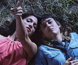 Film Still EXTRA TERRESTRES – EXTRA TERRESTRIALS von Regisseurin Carla Cavina mit Sunshine Logroño und Elba Escobar; Teresa (gespielt von Marisé Alvarez) liegt im Gras und schaut in den Himmel, in den ihre Schwester Andrea (gespielt von Laura Aleman) zeigt