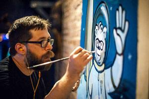 Film Still HAPPY: A SMALL FILM WITH A BIG SMILE von Michael Patrick McKinley über den Künstler Leonard Zimmerman alias Porkchop und seine Happy-Kampagne; Leonard malt ein Bild von einem Bär, der in einem Raumanzug winkend durch das blaue Weltall schwebt