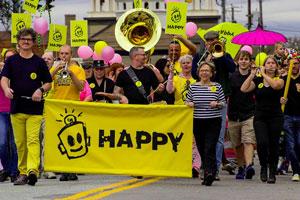 Film Still HAPPY: A SMALL FILM WITH A BIG SMILE von Michael Patrick McKinley über den Künstler Leonard Zimmerman alias Porkchop und seine Happy-Kampagne; eine Kampagnen-Parade mit auffälligem gelbem Banner und Blaskapelle zieht feierlich durch die Straßen