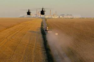 Film Still HARD WAY: THE ACTION MUSICAL von Daniel Vogelmann mit Oliver Tompsett, Hannah Britland, Charlie Anson; das Sondereinsatzkommando eilt mit einem Einsatzfahrzeug und zwei Helikoptern auf einen Industriekomplex zu