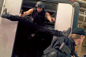 Film Still HARD WAY: THE ACTION MUSICAL von Daniel Vogelmann mit Oliver Tompsett, Hannah Britland, Charlie Anson; ein Mitstreiter aus dem Sondereinsatzkommando in schwarzer Kampfuniform springt im Spagat aus einem Einsatzfahrzeug