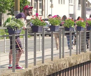 Film Still HOMØE: AUF DER SUCHE NACH GEBORGENHEIT von Bin Chen; der LSBT-Flüchtling Javid aus Azerbaijan steht an einem mit Blumen geschmückten Geländer in NRW