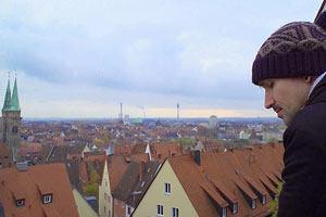 Film Still HOMØE: AUF DER SUCHE NACH GEBORGENHEIT von Bin Chen; der russische LSBT-Flüchtling Boris steht auf einem Balkon mit Blick über München