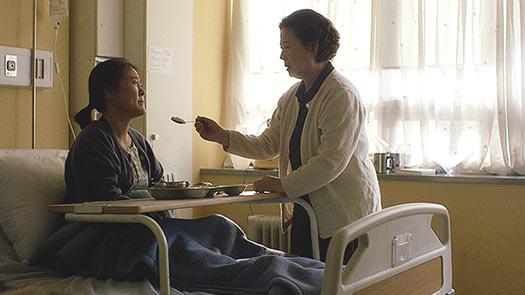 Film Still aus dem Kurzfilm FIRST LOVE von Ji-Sook Kang, Teil der Kurzfilmsammlung SMALL PALE BLUE GIRLS; eine koreanische Frau versucht ihrer geliebten Freundin, die im Krankenhaus liegt, Essen zu reichen