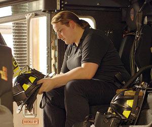 Film Still WOMAN ON FIRE von Julie Sokolow über die transsexuelle Feuerwehrfrau Brooke Guinan in New York; Brooke hält in einem Feuerwehrwagen sitzend einen Helm in der Hand