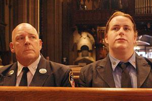 Film Still WOMAN ON FIRE von Julie Sokolow über die transsexuelle Feuerwehrfrau Brooke Guinan in New York; Brooke sitzt in ihrem Feuerwehr-Anzug in einer Kirche neben ihrem Vater
