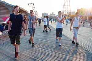Film Still BEACH RATS von Regisseurin Eliza Hittman; eine Gruppe von Jugendlichen spaziert die sommerliche Amüsier-Promenade auf Coney Island entlang