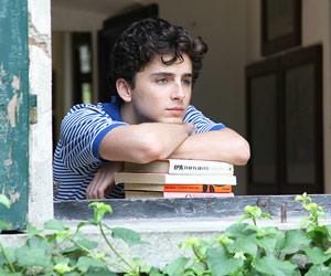 Film Still CALL ME BY YOUR NAME von Regisseur Luca Guadagnino; der Jugendliche Elio Perlman (gespielt von Timothée Chalamet) lehnt sich am offenen Fenster eines italienischen Landhauses auf einen Stapel Bücher