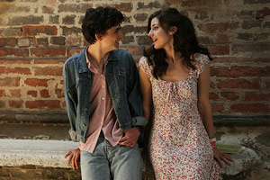 Film Still CALL ME BY YOUR NAME von Regisseur Luca Guadagnino; Elio Perlman (gespielt von Timothée Chalamet) steht eng neben Marzia (gespielt von Esther Garrel) vor einer Ziegelmauer