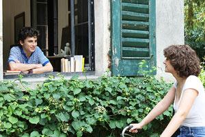 Film Still CALL ME BY YOUR NAME von Regisseur Luca Guadagnino; der Jugendliche Elio Perlman (gespielt von Timothée Chalamet) lehnt am offenen Fenster eines italienischen Landhauses neben einem Stapel Bücher und seine Freundin Marzia (gespielt von Esther Garrel) hält mit ihrem Fahrrad vor ihm