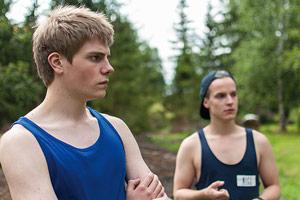 Film Still PIHALLA – SCREWED – AUF ZU NEUEN UFERN von Regisseur Nils-Erik Ekblom; der 17-jährige Miku (gespielt von Mikko Kauppila) und sein Freund Elias (gespielt von Valtteri Lehtinen) stehen mit Sport-Hemden im Wald