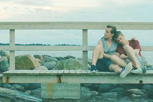 Film Still PIHALLA – SCREWED – AUF ZU NEUEN UFERN von Regisseur Nils-Erik Ekblom; der 17-jährige Miku (gespielt von Mikko Kauppila) sitzt an die Schulter seines Freunds Elias (gespielt von Valtteri Lehtinen) gelehnt auf einem Holzsteg am Strand
