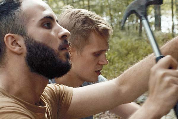 Film Still DIE HÜTTE AM SEE – A MOMENT IN THE REEDS, eine schwule Romanze zwischen einem Finnen und einem syrischen Flüchtling von Filmemacher Mikko Makela mit Janne Puustinen, Boodi Kabbani und Mika Melender; Leevi (gespielt von Janne Puustinen) arbeitet zusammen mit Tareq (Boodi Kabbani), der einen Hammer schwingt, an der Holz-Hütte