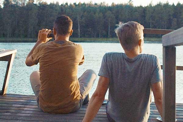 Film Still DIE HÜTTE AM SEE – A MOMENT IN THE REEDS, eine schwule Romanze zwischen einem Finnen und einem syrischen Flüchtling von Filmemacher Mikko Makela mit Janne Puustinen, Boodi Kabbani und Mika Melender; Leevi (gespielt von Janne Puustinen) sitzt mit Tareq (Boodi Kabbani), der mit seinem Smartphone ein Foto der Aussicht macht, auf einem Holzsteg am See