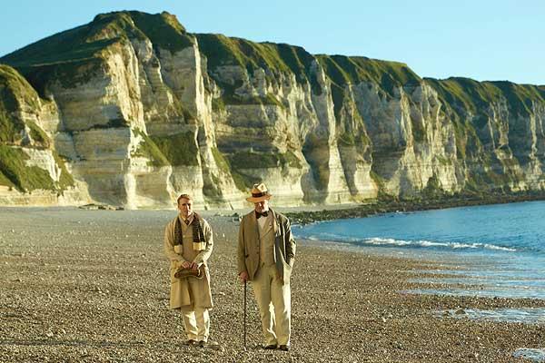 Film Still THE HAPPY PRINCE, Regiedebüt von Rupert Everett mit Colin Firth, Emily Watson, Tom Wilkinson und Béatrice Dalle; der schwule Autor und Dandy Oscar Wilde (gespielt von Everett) und sein Geliebter Robbie Ross (gespielt von Edwin Thomas) gehen einen Strand vor einer Felsenküste entlang