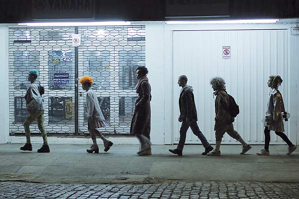 Film Still DAS NEST - THE NEST - O NINHO, queere Mini-Serie der brasilianischen Teddy-Gewinner Filipe Matzembacher & Marcio Reolon; eine Gruppe von schwulen, queeren und genderqueeren jungen Menschen geht nachts im Gänsemarsch hintereinander vor einem weißen Gebäude vorbei