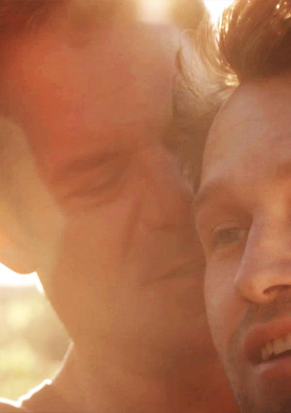 Film Still RETAKE von Regisseur und Autor Nick Corporon mit Devon Graye, Derek Phillips und Chris Pudlo; Jonathan (gespielt von Tuc Watkins) steht im Sonnenschein hinter seinem schwulen Lover