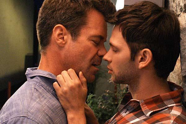 Film Still RETAKE von Regisseur und Autor Nick Corporon mit Derek Phillips und Chris Pudlo; Jonathan (gespielt von Tuc Watkins) und der Stricher Adam (gespielt von Devon Graye) stehen eng beieinander, als wollten sie sich gleich küssen