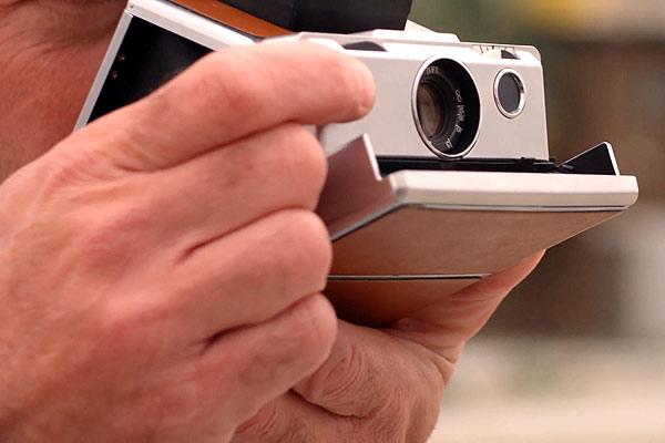 Film Still RETAKE von Regisseur und Autor Nick Corporon mit Tuc Watkins, Devon Graye, Derek Phillips und Chris Pudlo; jemand hält eine Sofortbild-Kamera für ein Foto hoch
