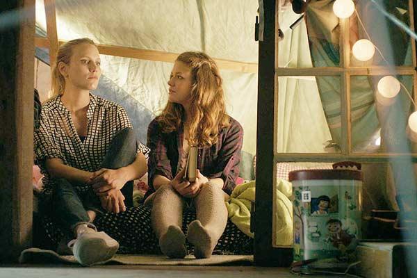 Film Still ZWISCHEN SOMMER UND HERBST, eine lesbische romantische Dramödie von Daniel Manns aus Bielefeld in NRW; Lena (gespielt von Linn Reusse) und Eva (gespielt von Isabel Thierauch) sitzen abends in einem Baumhaus