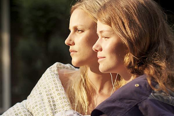 Film Still ZWISCHEN SOMMER UND HERBST, eine lesbische romantische Dramödie von Daniel Manns aus Bielefeld in NRW; Eva (gespielt von Isabel Thierauch) und Lena (gespielt von Linn Reusse) sitzen versetzt nebeneinander und schauen in den Sonnenuntergang