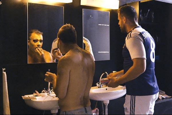 Film Still TACKLING LIFE, ein Dokumentarfilm von Regisseur Johannes List über das Rugby-Team Berlin Bruisers; in einem Badezimmer steht ein Rugby-Spieler in Sportkleidung, während sich ein Mitspieler vor dem Spiegel schminkt