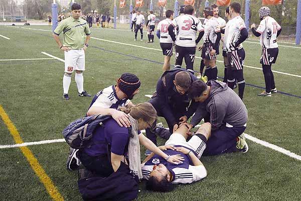 Film Still TACKLING LIFE, ein Dokumentarfilm von Regisseur Johannes List über das Rugby-Team Berlin Bruisers; ein verletzter Spieler liegt auf dem Rasen und wird behandelt, während einige Sportler um ihn stehen