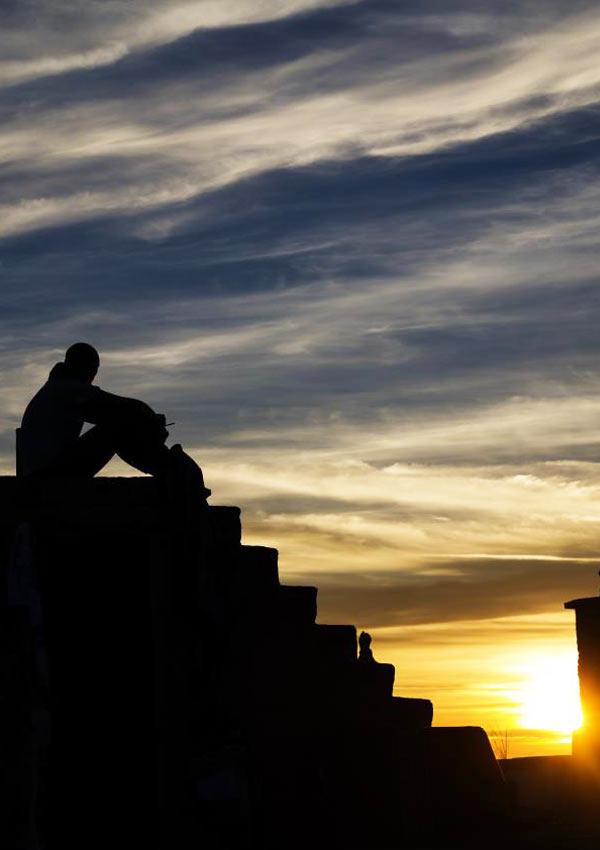 Film Poster AEFFETTO DOMINO von Regisseur, Autor, Ko-Editor und Hauptdarsteller Fabio Massa aus Italien, 2016; Lorenzo (gespielt von Fabio Massa) sitzt auf Stufen vor einem Abendhimmel mit Sonnenuntergang und zeichnet sich als Umriss ab