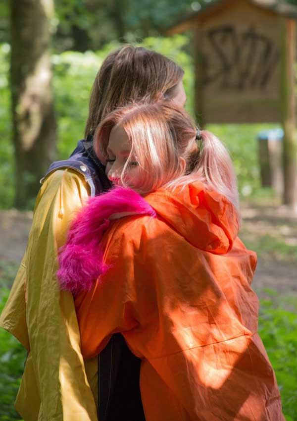Film Still BEARKITTENS von Regisseur Lars Henriks und Produzent Nisan Arikan aus Deutschland, 2018; zwei Jugendliche, die Sozialstunden ableisten müssen, umarmen sich in knallig-bunten Regenjacken