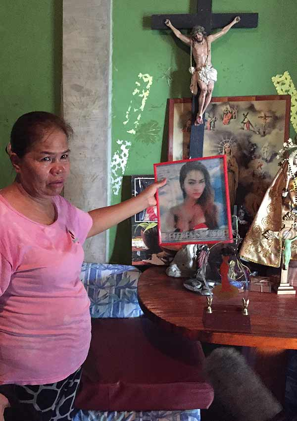 Film Still CALL HER GANDA von Regisseur, Produzent und Ko-Autor PJ Raval aus USA und Philippinen, 2018, über den Mord an Transfrau Jennifer Laude durch einen US-Marine; Jennifers Mutter zeigt ein Foto unter einem christlichen Kreuz