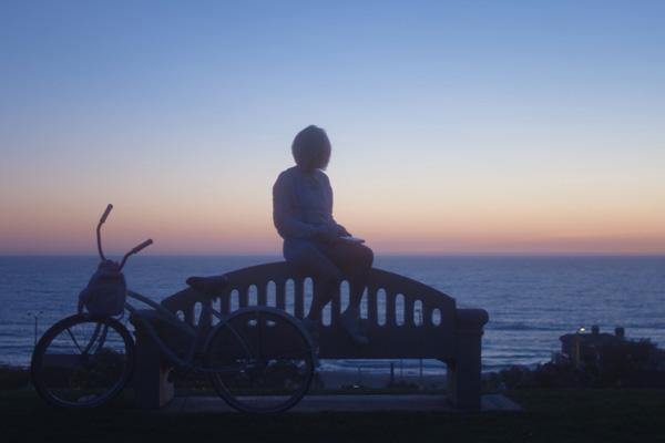 Film Still DADDY ISSUES von Regisseurin und Cutterin Amara Cash aus den USA, 2018; Maya Mitchell (gespielt von Madison Lawlor) sitzt neben ihrem Fahrrad auf einer Bank vor einem Ozean-Ausblick und einem spektakulären Sonnenuntergang