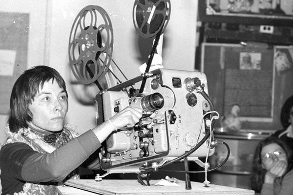 Film Still der lesbischen Doku DYKES, CAMERA, ACTION! von Regisseurin, Produzentin und Editorin Caroline Berler aus USA, 2018; ein altes Schwarz-Weiß-Bild von Filmemacherin Barbara Hammer, die einen 16-mm-Film vorführt