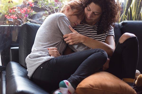 Film Still EVA + CANDELA von Autorin, Regisseurin und ausführender Produzentin Ruth Caudeli aus Kolumbien, 2018; Eva (gespielt von Silvia Varón) schmiegt sich Trost suchend auf dem Sofa an die Schulter Candela (Alejandra Lara)