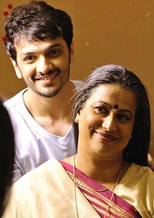 Film Still EVENING SHADOWS von Regisseur, Produzent und Ko-Autor Sridhar Rangayan aus Indien, 2018; Kartik (gespielt von Devansh Doshi) steht hinter seiner Mutter Vasudha (gespielt von Mona Ambegaonkar) und sie lächeln sich an