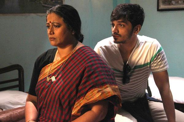 Film Still EVENING SHADOWS von Regisseur, Produzent und Ko-Autor Sridhar Rangayan aus Indien, 2018; Kartik (gespielt von Devansh Doshi) hockt in einem Hotelzimmer hinter seiner nachdenklich dreinschauenden Mutter Vasudha (gespielt von Mona Ambegaonkar)