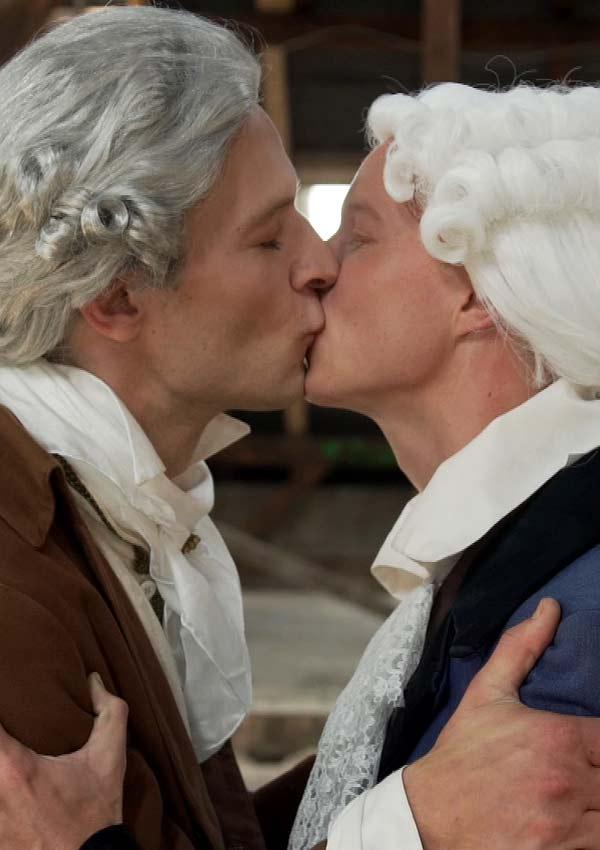 Film Still MÄNNERFREUNDSCHAFTEN von Regisseur Rosa von Praunheim über die Freundschaften unter Weimarer Schriftstellern; zwei Schauspieler mit weißen Perücken küssen sich leidenschaftlich auf den Mund