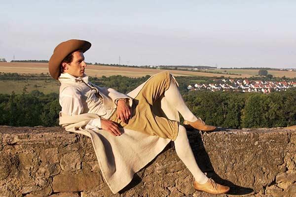 Film Still MÄNNERFREUNDSCHAFTEN von Regisseur Rosa von Praunheim über die Freundschaften unter Weimarer Schriftstellern; ein Schauspieler sitzt in historischem Kostüm und Hut auf einer Mauer auf einer Anhöhe vor einem Dorf im Wald