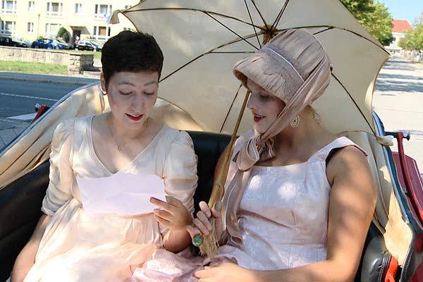 Film Still MÄNNERFREUNDSCHAFTEN von Regisseur Rosa von Praunheim über die Freundschaften unter Weimarer Schriftstellern; zwei Schauspielerinnen sitzen mit beigen Kleidern, Kappe und Sonnenschirm auf der Rückbank eines Wagens