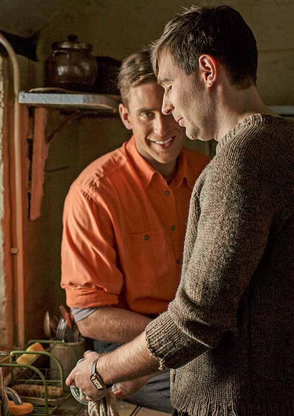 Film Still MAN IN AN ORANGE SHIRT von Regisseur Michael Samuels, BBC-Zweiteiler aus GB, 2017; Michael Berryman (gespielt von Oliver Jackson-Cohen) steht in orangem Hemd neben Maler und Thomas March (gespielt von James McArdle), der im Cottage den Abwasch macht