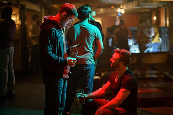 Film Still MAN IN AN ORANGE SHIRT von Regisseur Michael Samuels, BBC-Zweiteiler aus GB, 2017; Tierarzt Adam (gespielt von Julian Morris) steht mit seinem Smartphone in der Hand in einer Bar