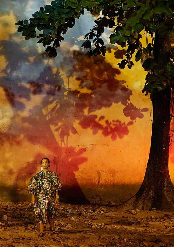 Film Still OBSCURO BARROCO von Regisseurin Evangelia Kranioti, eine französisch-griechische Doku über den Straßenkarneval von Rio de Janeiro; eine Frau geht vor einer hohen Mauer, auf die Feuerwerk bunte Schatten eines Baumes wirft