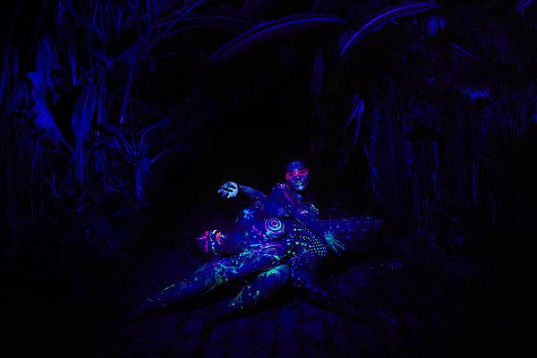 Film Still OBSCURO BARROCO von Regisseurin Evangelia Kranioti, eine französisch-griechische Doku über den Straßenkarneval von Rio de Janeiro; mit Neonfarben bemalte Körper räkeln sich zwischen Vegetation