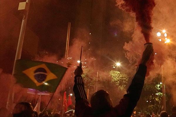 Film Still OBSCURO BARROCO von Regisseurin Evangelia Kranioti, eine französisch-griechische Doku über den Straßenkarneval von Rio de Janeiro; Feiernde schwenken nachts die brasilianische Flagge und versprühen bunten Nebel