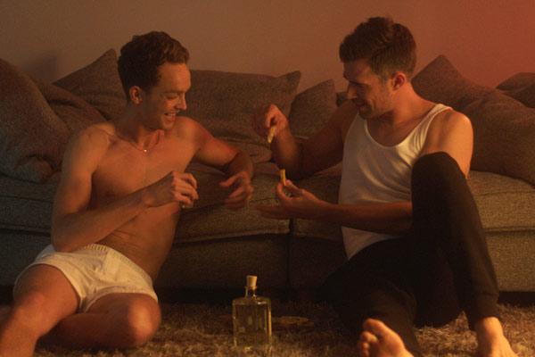 Film Still SODOM von Regisseur und Autor Mark Wilshin aus England, 2017; Michael (gespielt von Jo Weil) und Will (gespielt von Pip Brignall) stoßen auf dem Boden vor dem Sofa sitzend mit Tequila an