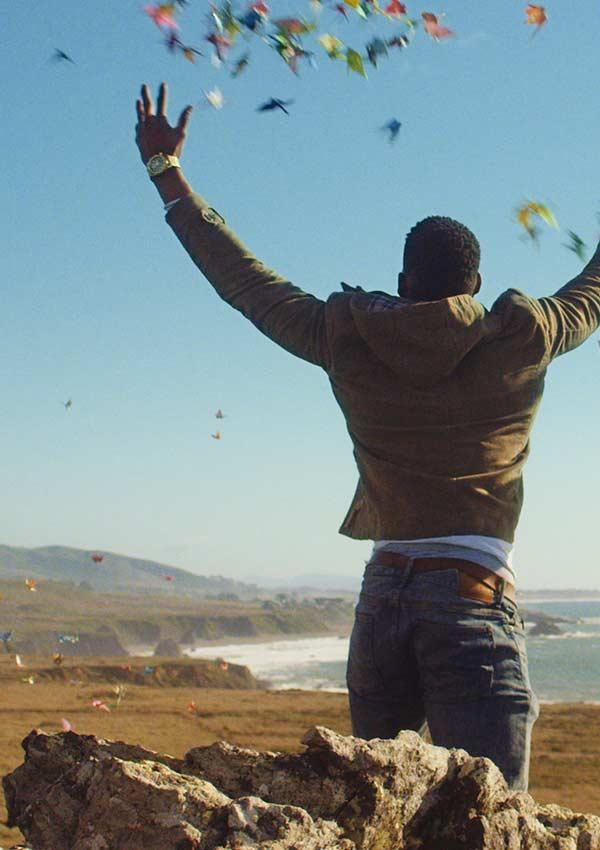 Film Still THE DEEP SKY von Regisseur, Autor, Produzent und Kameramann Frazer Bradshaw aus USA, 2017; Arlan (gespielt von Kelechi Nwadibia) wirft an einer Klippe Origami-Kraniche in den Himmel